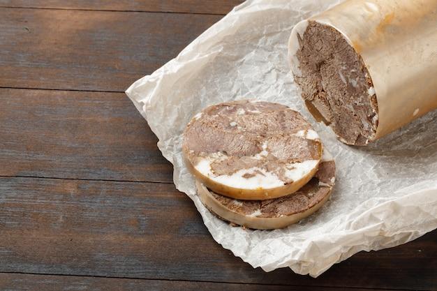 Gehakte vleesworst op houten bord close-up