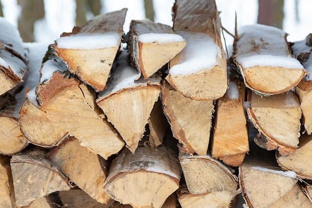 Gehakte voorraad brandhout onder sneeuw op straat. brandhout voor open haard en bbq