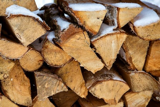 Gehakte voorraad brandhout onder sneeuw op straat. textuur