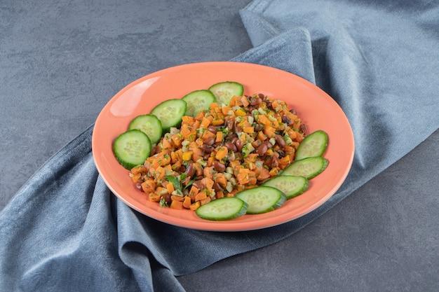 Gehakte wortelen, bonen en komkommer op een bord op de handdoek naast hele wortelen, op het marmeren oppervlak.