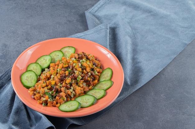 Gehakte wortelen, bonen en komkommer op een bord op de handdoek naast hele wortels op het marmeren oppervlak