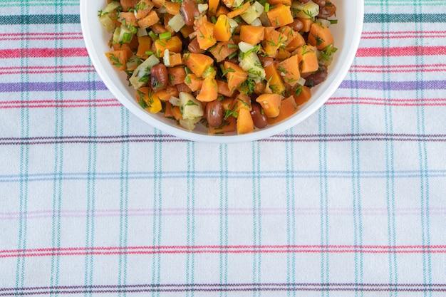 Gehakte wortelen en bonen in een kom op handdoek naast hele wortelen op het marmeren oppervlak