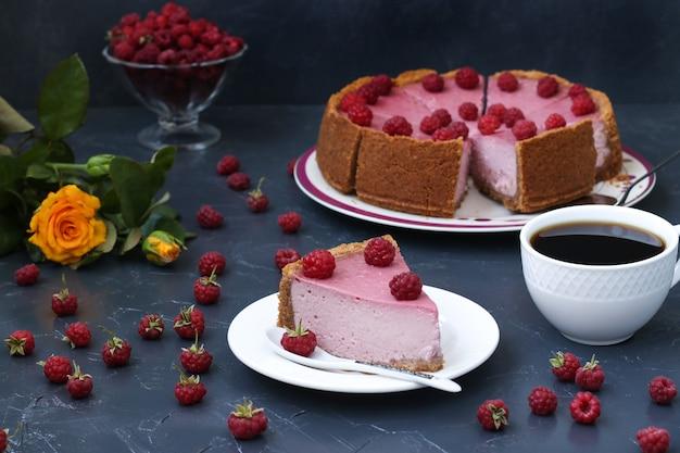 Gehakte zelfgemaakte frambozen cheesecake in porties op een bord, gelegen op een donkere ondergrond, horizontaal formaat