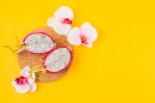 Gehalveerd draakfruit op cork onderlegger voor glazen met roze orchideebloem op gele achtergrond