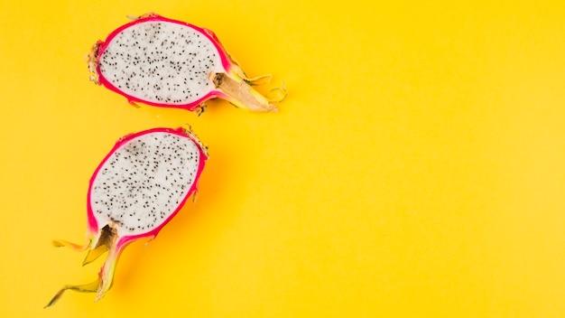 Gehalveerd draakfruit op gele achtergrond