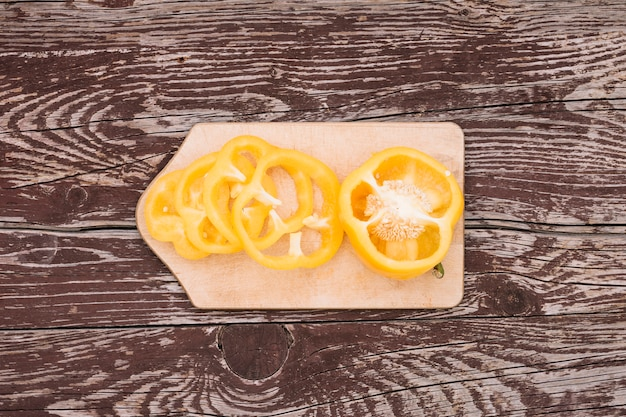 Gehalveerd en plakjes gele paprika op snijplank over de houten textuur achtergrond