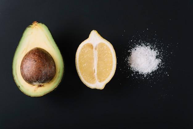 Gehalveerde avocado en citroen in de buurt van zout op zwart oppervlak