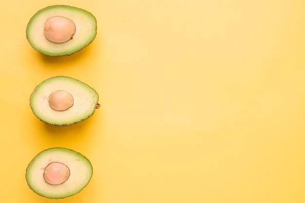 Gehalveerde avocado op gele achtergrond