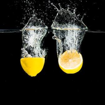 Gehalveerde citroenen die in waterplons vallen over zwarte achtergrond