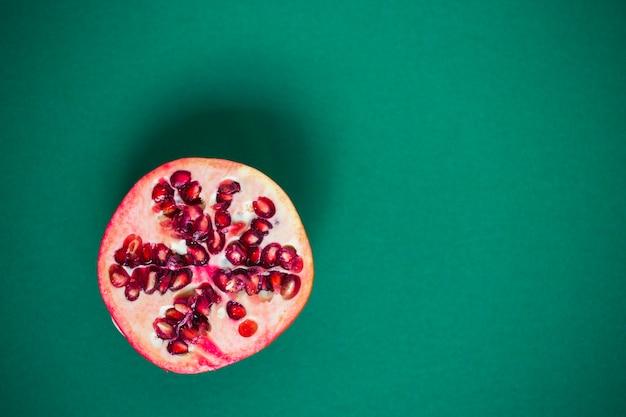 Gehalveerde granaatappel op groene achtergrond