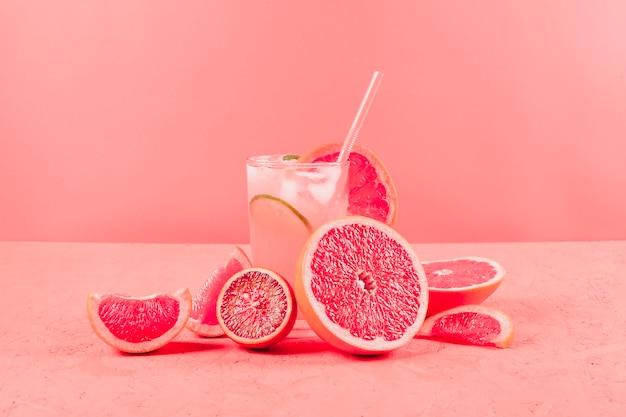 Gehalveerde grapefruits en glas sap op koraalachtergrond