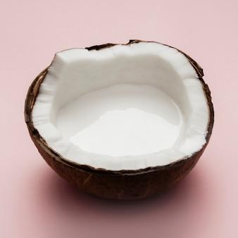 Gehalveerde kokosnoot op roze achtergrond