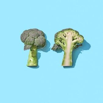 Gehalveerde rauwe biologische broccoli op een blauwe achtergrond met reflectie van de schaduwen en kopieerruimte. gezond vegetarisch eten. bovenaanzicht