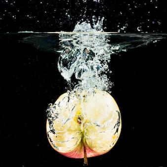 Gehalveerde verse appel die in schoon water tegen zwarte achtergrond valt