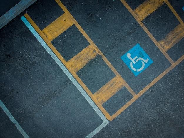 Gehandicapt blauw parkerenteken dat op donker asfalt wordt geschilderd. lege gehandicaptenruimten op zwarte.