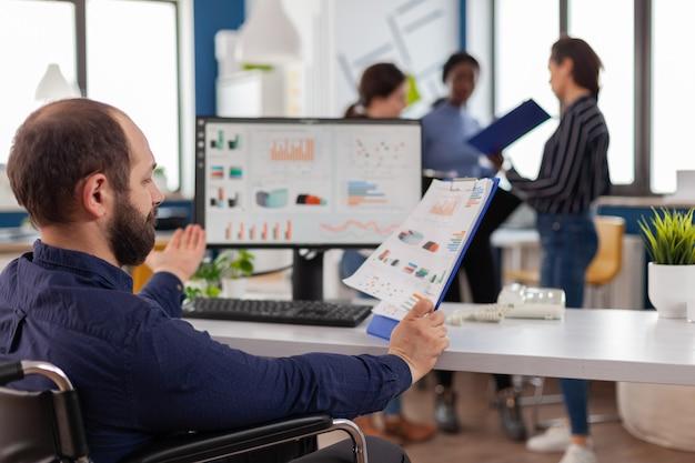 Gehandicapt marketingmanagerproject zit in een rolstoel in een startkantoor dat controlerapporten leest