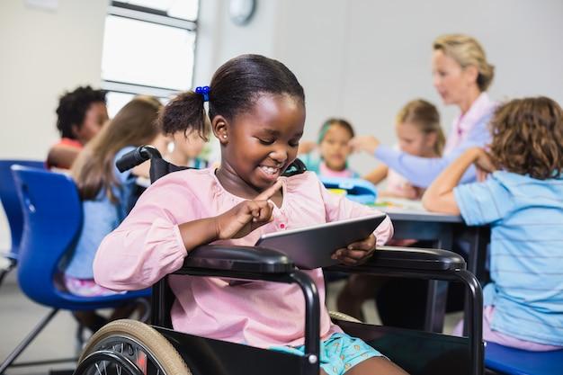 Gehandicapt schoolmeisje dat digitale tablet gebruikt
