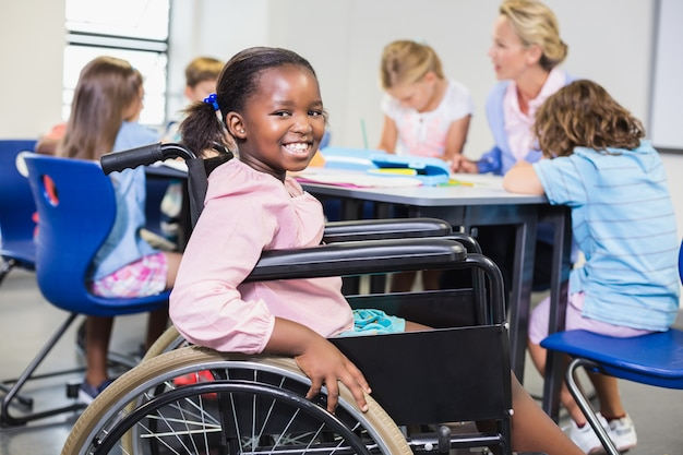 Gehandicapt schoolmeisje dat in klaslokaal glimlacht
