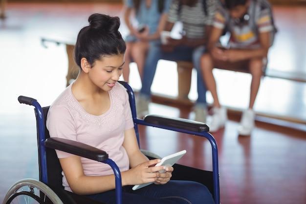 Gehandicapt schoolmeisje met behulp van digitale tablet met klasgenoten op de achtergrond