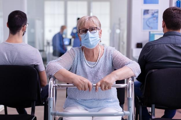 Gehandicapte bejaarde met een looprek die bij de receptie van het ziekenhuis naar de camera kijkt
