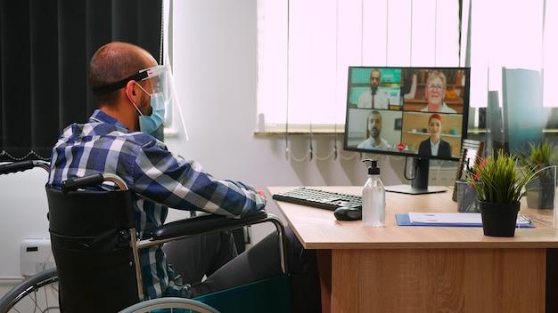 Gehandicapte financiële expert in rolstoel die praat met partners die masker en vizier dragen tijdens videoconferentie in bedrijfskantoor. geïmmobiliseerde freelancer die in bedrijf werkt met respect voor sociale afstand
