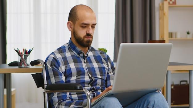 Gehandicapte freelancer in woonkamer in rolstoel die aan laptop werkt.