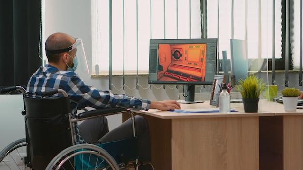 Gehandicapte game-ontwikkelaar zittend in rolstoel met beschermingsmasker aan het werk bij nieuw project vanuit nieuw normaal studiokantoor tijdens covid-19 pandemie. geïmmobiliseerde man met respect voor sociale afstand.