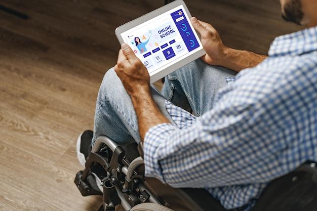 Gehandicapte jonge afro-amerikaanse man die in een rolstoel zit en digitale tablet gebruikt