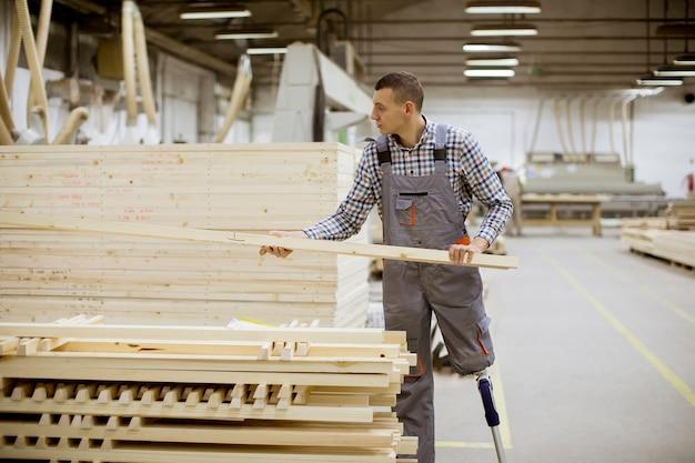 Gehandicapte jonge man met een kunstbeen werkt in de meubelfabriek