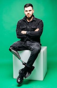 Gehandicapte jonge mens met prothetisch been, kunstmatig lidmaatconcept op groene muur
