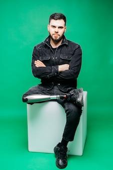 Gehandicapte jonge mens met prothetische beenzitting in studio over groene muur, kunstmatig lidmaatconcept