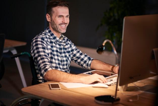 Gehandicapte man aan het werk met technologie in thuiskantoor