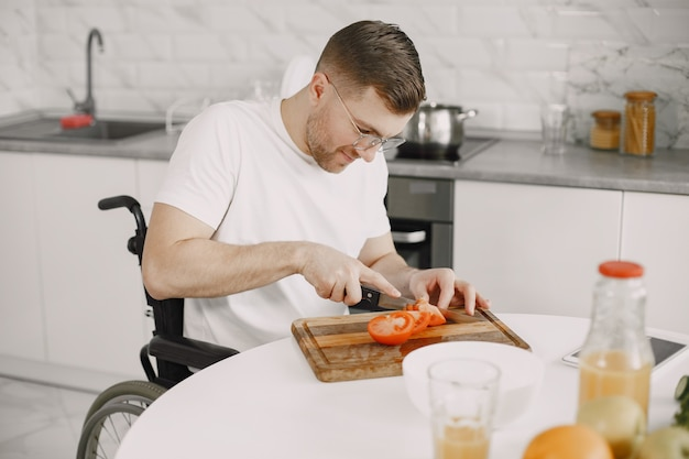Gehandicapte man bereiden van voedsel in de keuken. groenten snijden.