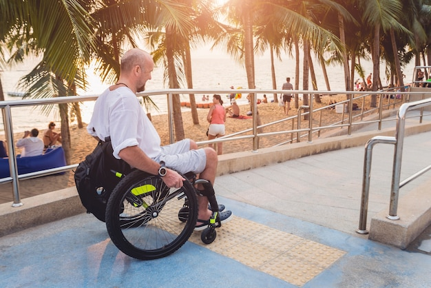 Gehandicapte man in een rolstoel beweegt op een helling naar het strand.