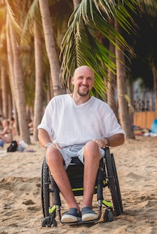 Gehandicapte man in een rolstoel met zijn familie op het strand.