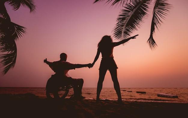 Gehandicapte man in een rolstoel met zijn vrouw op het strand. silhouetten bij zonsondergang