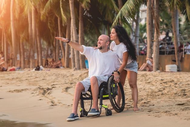 Gehandicapte man in een rolstoel met zijn vrouw op het strand.