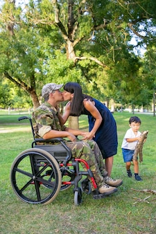 Gehandicapte man in militair uniform zoenen vrouw terwijl hun kleine zonde brandhout voor kampvuur in park dragen. gehandicapte veteraan of familie buitenshuis concept