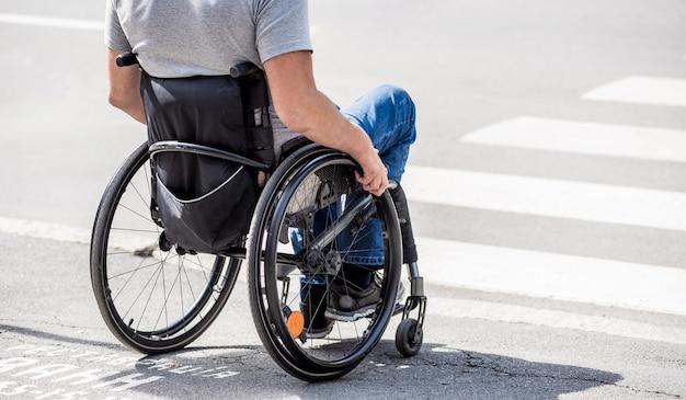 Gehandicapte man in rolstoel bereidt zich voor om de weg over te steken op voetgangersoversteekplaats.