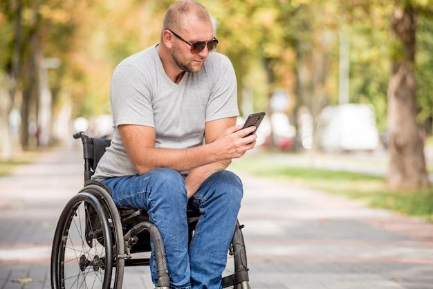 Gehandicapte man in rolstoel bij het parksteeg gebruikt een smartphone