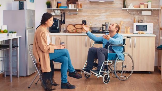 Gehandicapte man in rolstoel die een geschil heeft met zijn vrouw in de keuken. man met verlamming handicap handicap gehandicapte moeilijkheden om hulp te krijgen voor mobiliteit van liefde en relatie