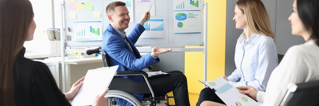 Gehandicapte man in rolstoel die grafieken op schoolbord toont aan zijn studenten