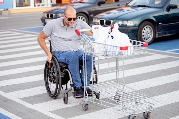 Gehandicapte man in rolstoel die kar voor zich uit duwt bij supermarktparkeren
