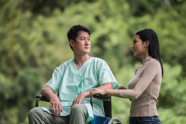Gehandicapte man in rolstoel en vriendin in het park
