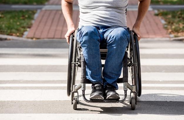 Gehandicapte man in rolstoel kruising straatweg
