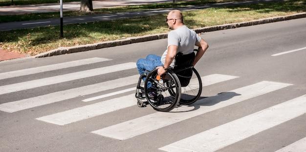 Gehandicapte man in rolstoel kruising straatweg.