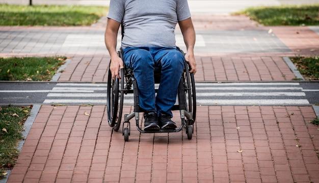 Gehandicapte man in rolstoel voorbereiden om de weg over te steken op voetgangersoversteekplaats