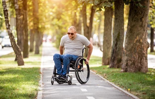 Gehandicapte man in rolstoelwandeling op het steegje van het park