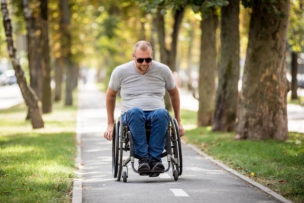 Gehandicapte man in rolstoelwandeling op het steegje van het park.