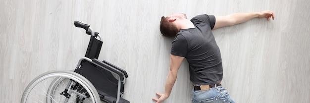 Gehandicapte man ligt op de vloer naast rolstoeldepressie bij mensen met een handicap concept